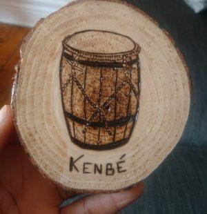 Petit tableau pyrogravé représentant un tambour ka et le mot créole kenbé