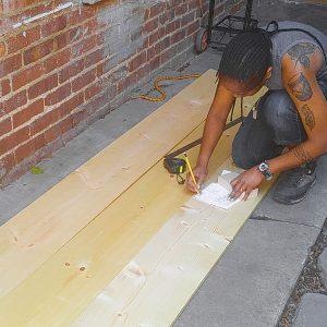 Photo de moi en train de mesurer des planches pour créer ma bibliothèque déstructurée